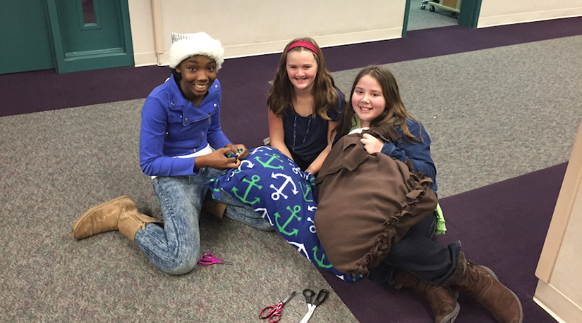 Three students make dog beds to bring to the Indy Humane Society.