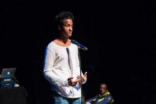 A student performs an original poem at the Guthrie Theater.